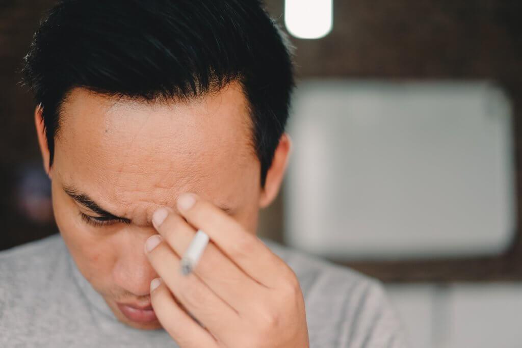 タバコを持ちながら頭を痛める男性